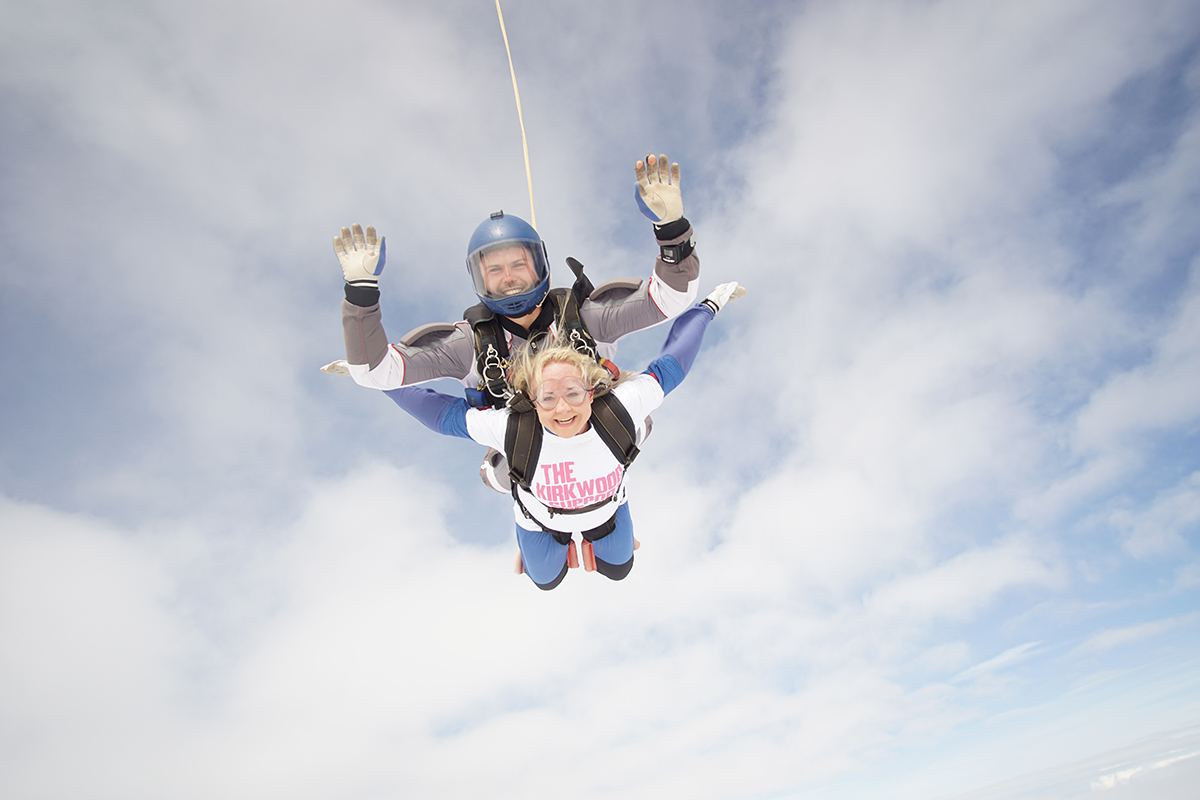 Cubicle Centre's Rachel Stanley tandem skydiving in a cloudy sky